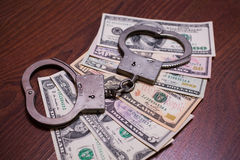 Dollar bills and handcuffs Stock Images