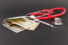 Dollar bills insulin syringe and stethocope. On dark black background Stock Photos