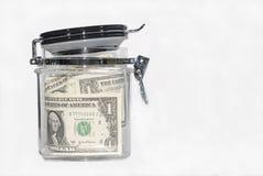 Dollar bills in a kitchen storage jar Royalty Free Stock Images