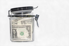 US One Dollar bills in a kitchen storage jar, saving concept, white background. Several dollar bills in a kitchen storage jar stock photography