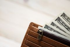 Dollar bills and leather wallet Stock Photos