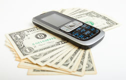 Dollar bills and mobile telephone Stock Photos