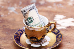 Dollar bills money roll. In colored cup on wooden background Royalty Free Stock Photo