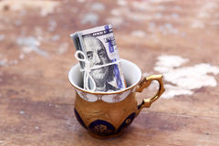 Dollar bills money roll. In colored cup on wooden background Royalty Free Stock Photography