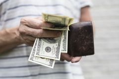 100 dollar bills with an old worn wallet stock photos