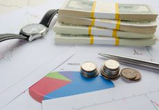 Dollar bills in packs, coins  clock calculator and graphics Stock Image
