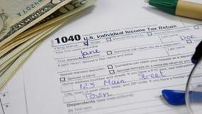 Dollar bills, Pen and Glasses on 1040 Tax Return Form