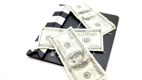 Dollar bills placed on a cinema clap. Against a white background stock footage