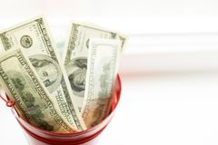 Dollar bills in red pail. on white window.light background. place for text. top view. a lot of money royalty free stock image