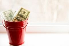 Dollar bills in red pail. on white window.light background. top view. a lot of money royalty free stock photography