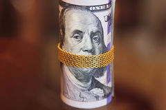 Dollar bills roll money with gold chain on mouth of franklin Stock Image