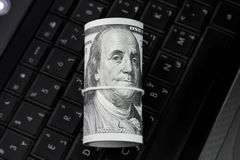 Dollar bills roll money on laptop keyboard Stock Image