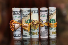 Dollar bills rolls money with gold jewelry rings  Royalty Free Stock Image