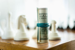 Dollar bills standing on chess board in place of tower piece Royalty Free Stock Image
