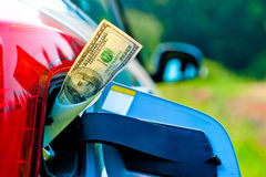 Dollar bills sticking out of gas tank of a modern car Stock Photos