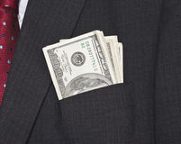 Dollar bills in suit pocket. A suit pocket full of american dollars, red tie Stock Photos