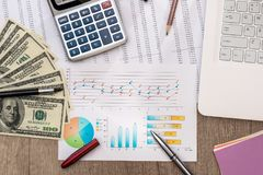 Dollar bills on a table with graph chart and laptop, pen. And calculator Royalty Free Stock Image
