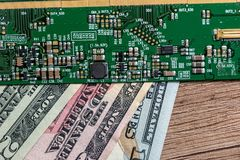 Dollar bills from technology. green motherboard. Close up Royalty Free Stock Images