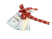 Dollar bills tied with red ribbon and decorated as a gift on a w. Hite background Royalty Free Stock Photography