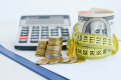 Dollar bills tied up with yellow measuring tape suggesting measurement of financial status Stock Photos