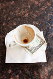 Dollar bills under a coffee Royalty Free Stock Photos