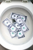 Dollar bills in a white toilet Stock Photos