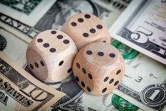 Dollar bills and wooden dice on them Stock Image
