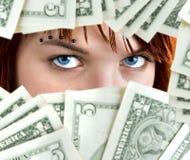 Dollar blue eyes. Piercing blue eyes of a cute redhead girl peeking through Dollar banknotes Royalty Free Stock Image