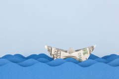 Dollar boat swimming on paper waves Stock Photography