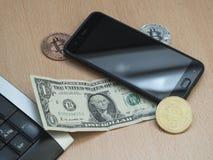 Dollar bredvid bitcoins, nedanför mobil och tangentbordet fotografering för bildbyråer