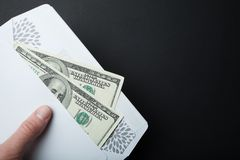 Dollar bribe in an envelope on a black background, empty space for text royalty free stock photo