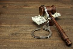 Dollar Cash, handcuffs and judge gavel on wood table Royalty Free Stock Photos