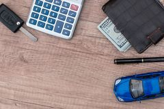 Dollar cash in wallet and car remote key. On wooden table Stock Photos
