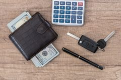 Dollar cash in wallet and car remote key. On wooden table Stock Image