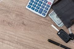 Dollar cash in wallet and car remote key. On wooden table Royalty Free Stock Photos