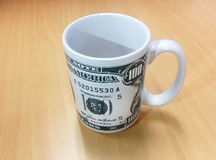 Dollar Coffee Mug. Dollar printed on mug with wood pattern office desk Royalty Free Stock Photo