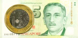 1 dollar coin against 5 singapore dollar bank note obverse stock photography