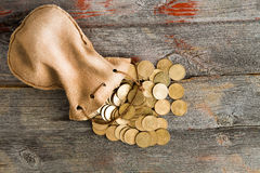Dollar coins spilling out of a drawstring pouch. Pile of dollar coins spilling out of a drawstring pouch onto a rustic old weathered wooden table, view from Royalty Free Stock Image