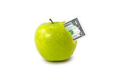 Dollar coming out from green apple Stock Photos