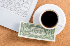 A dollar on a cup of coffee. And laptop place on wooden board Stock Photography