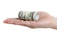 Dollar currency in hand. Human hand holding rolled up paper dollar currency Stock Images