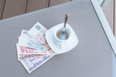 Dollar de Hong Kong, de l'Indonésie, de la Malaisie, du thailandais, de Singapour et tasse de café vide sur une table en verre de image libre de droits