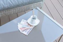 Dollar de Hong Kong, de l'Indonésie, de la Malaisie, du thailandais, de Singapour et tasse de café vide sur une table en verre de photographie stock libre de droits