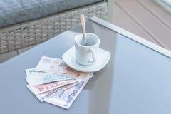 Dollar de Hong Kong, de l'Indonésie, de la Malaisie, du thailandais, de Singapour et tasse de café vide sur une table en verre de image stock