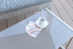 Dollar de Hong Kong, de l'Indonésie, de la Malaisie, du thailandais, de Singapour et tasse de café vide sur une table en verre de images stock