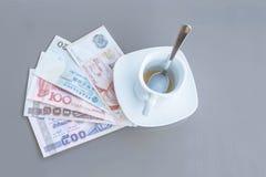 Dollar de Hong Kong, de l'Indonésie, de la Malaisie, du thailandais, de Singapour et tasse de café vide sur une table en verre de photos libres de droits