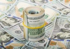 Dollar in der Rolle auf Geldhintergrund Stockfotografie
