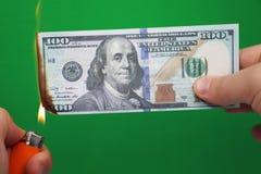 100 Dollar, die auf einem grünen Hintergrund brennen Konzept des Abwärtstrends bei der Wirtschaft und beim Verlust lizenzfreie stockfotos
