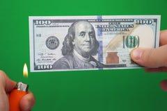 100 Dollar, die auf einem grünen Hintergrund brennen Konzept des Abwärtstrends bei der Wirtschaft und beim Verlust lizenzfreie stockbilder