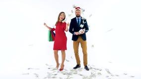 Dollar, die auf formal gekleideten Mann und Frau im Santa Claus-Hut fallen Lassen Sie ` s gehen Urlaubseinkäufe und feiern stock video